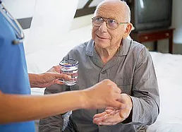 home care nurse helping with medication management and administring medication to senior